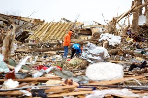 Workers pick through debris scattered following a deadly tornado in Joplin, MO.