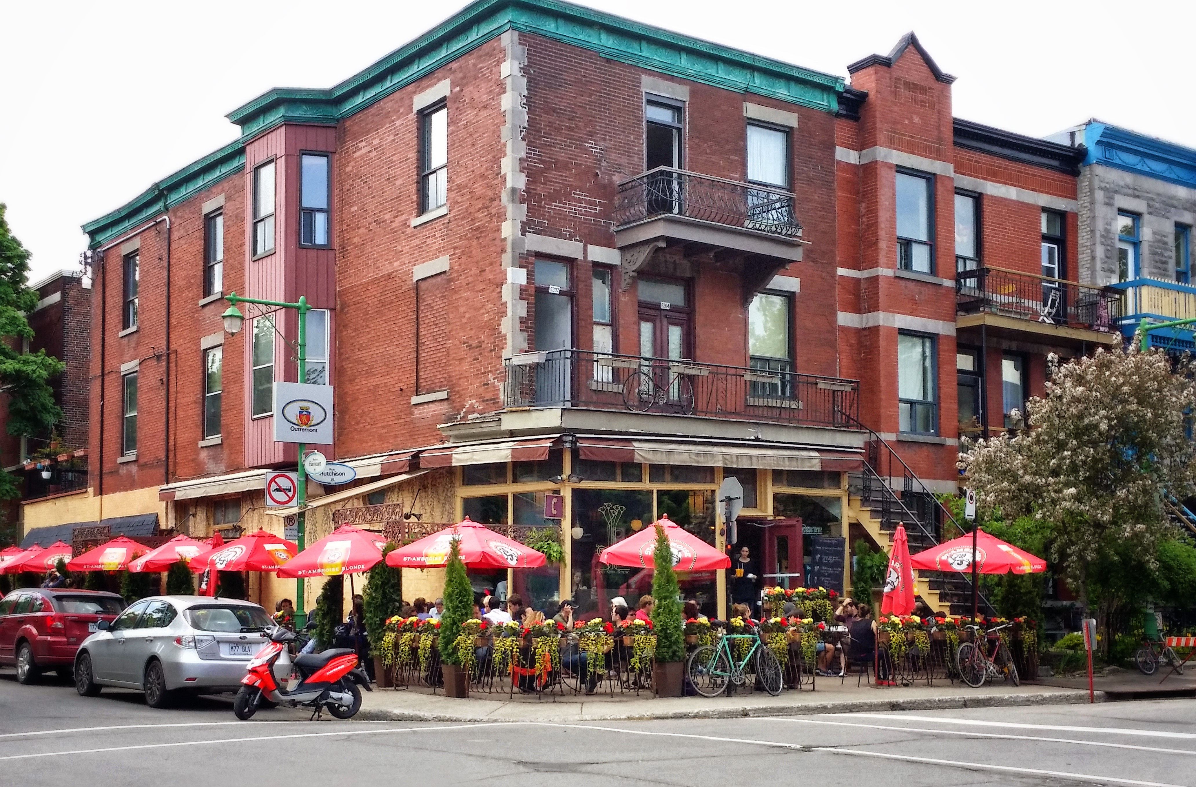 Diners at an outside eating area of a brick, two story street corner restaurant.