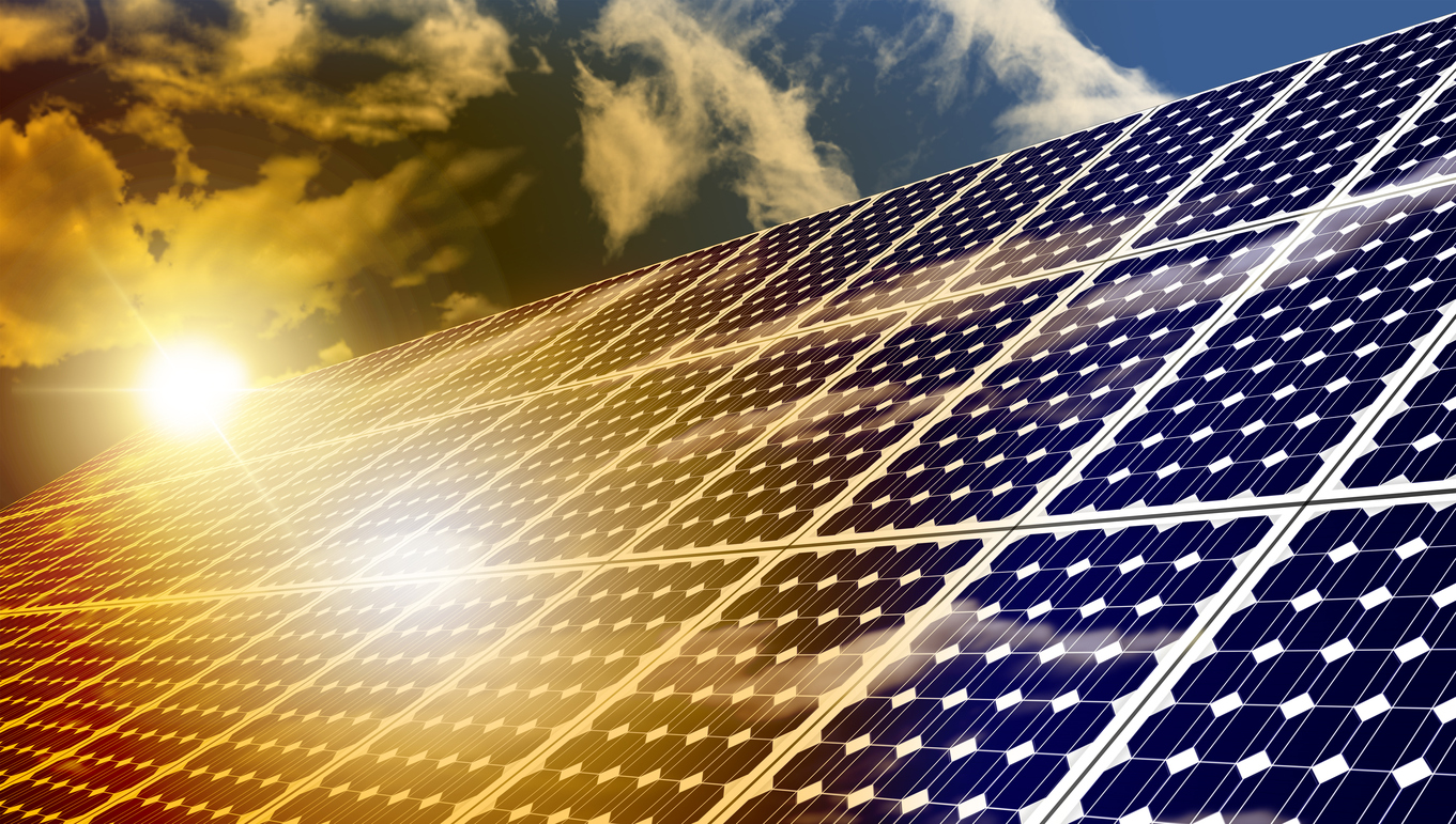 Photograph of solar panels in the foreground, reflecting the sunlight.