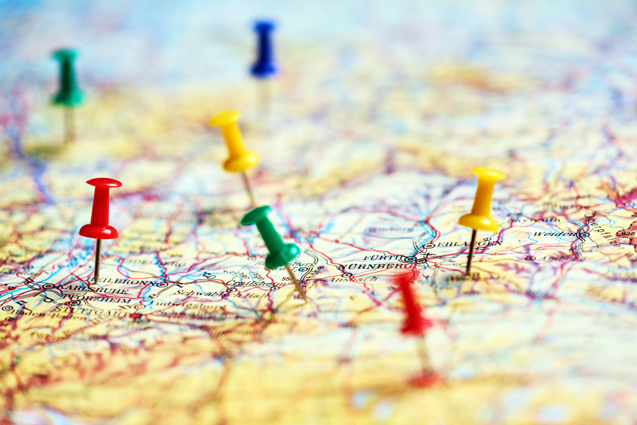 Colorful pins marking different destinations on a paper map.