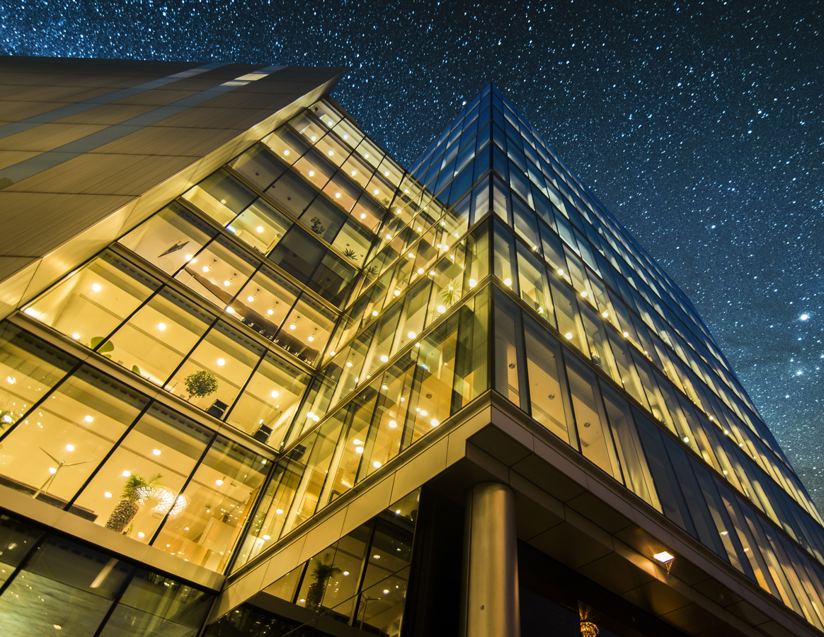 A block of offices at night; perspective is looking up from ground level to the night sky.
