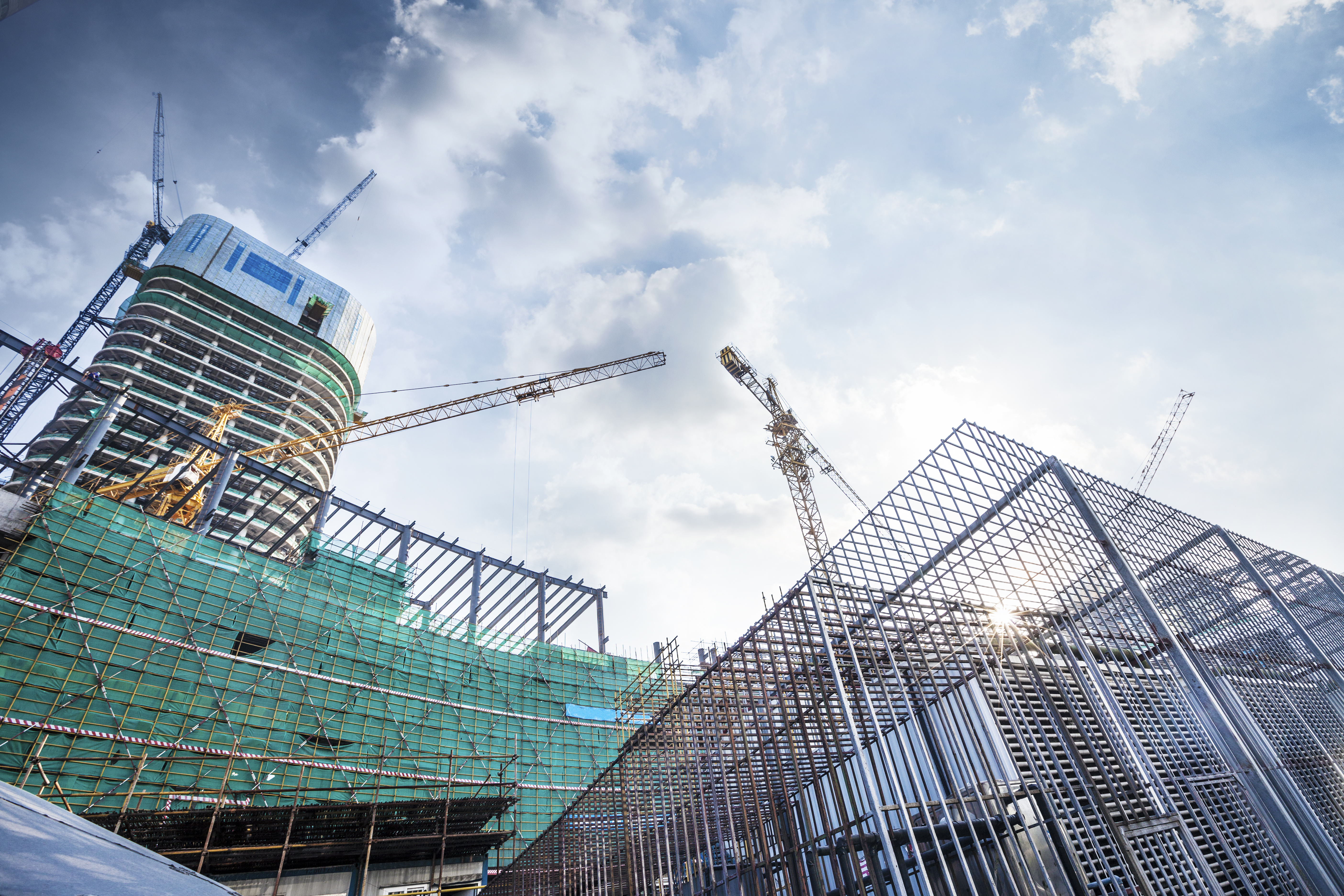A view from below of an industrial building construction site with cranes in a city