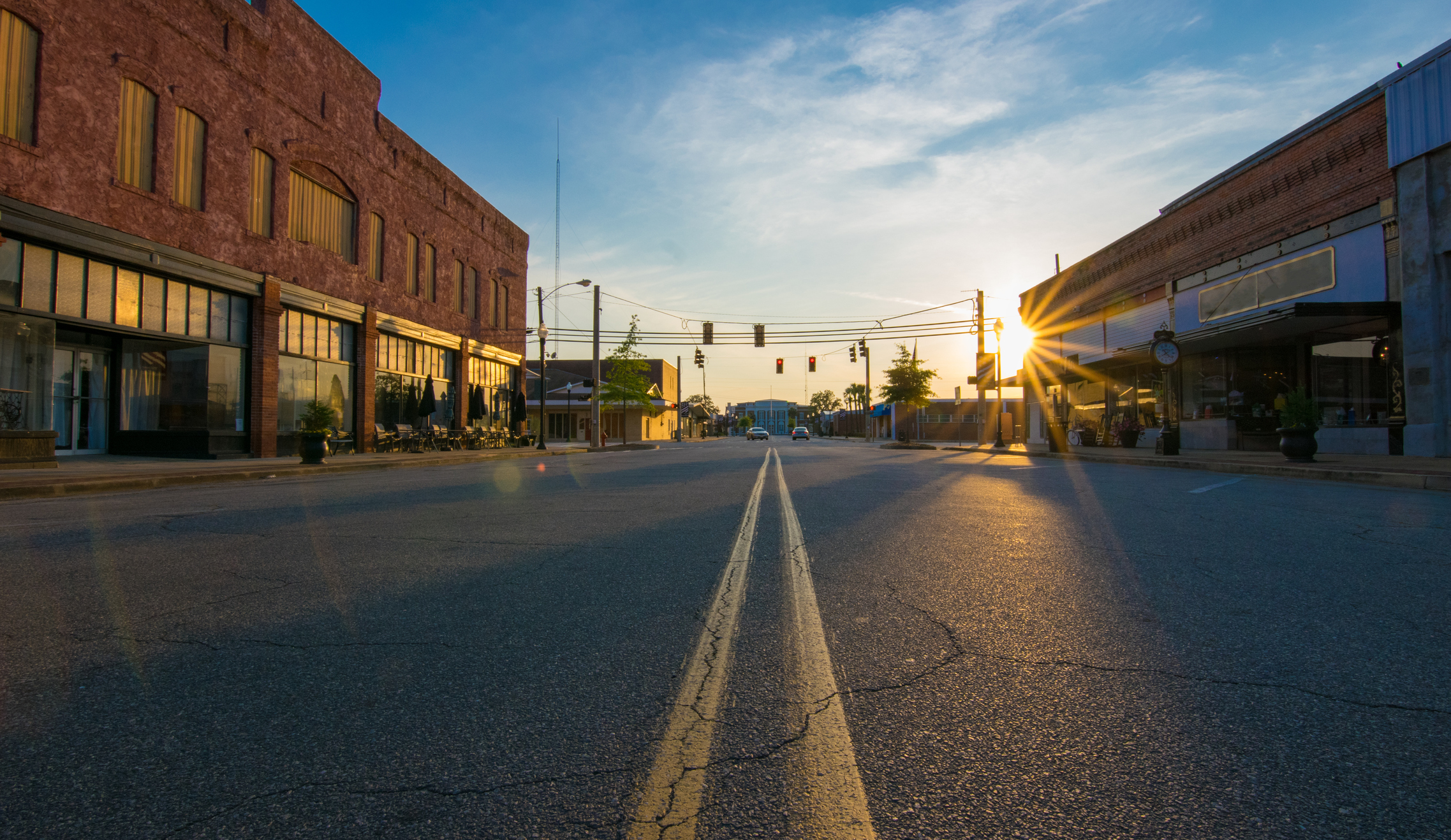 Storefronts at sunset in the middle of an empty road in downtown in a small town.
