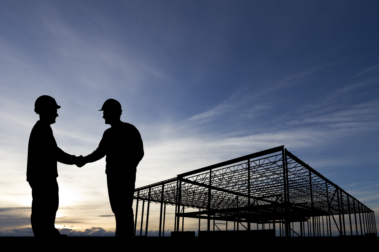 Silhouette of two people wearing hardhats and shaking hands on a construction jobsite.