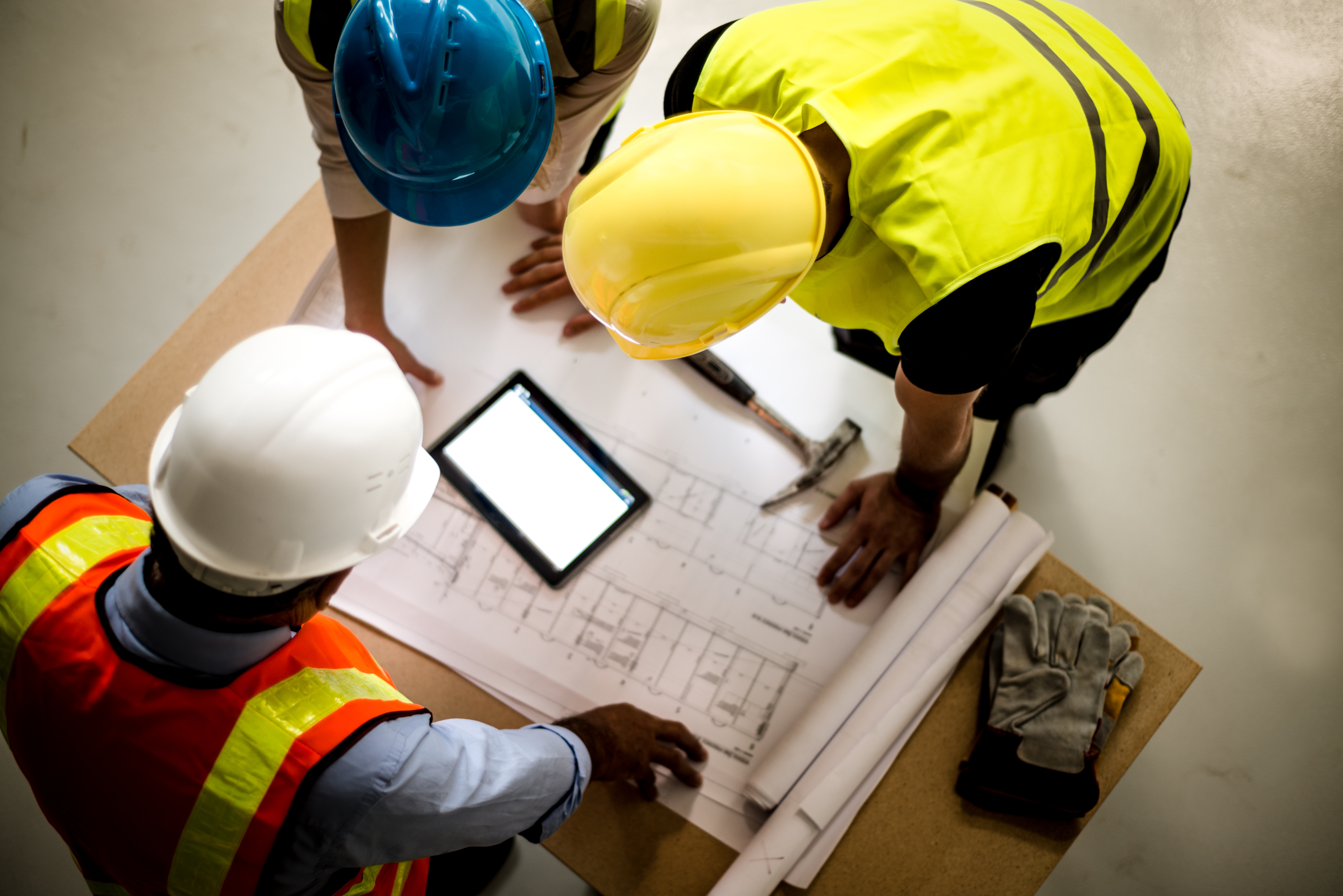 A view from above of three construction workers gathered around a table looking over construction plans and a tablet.