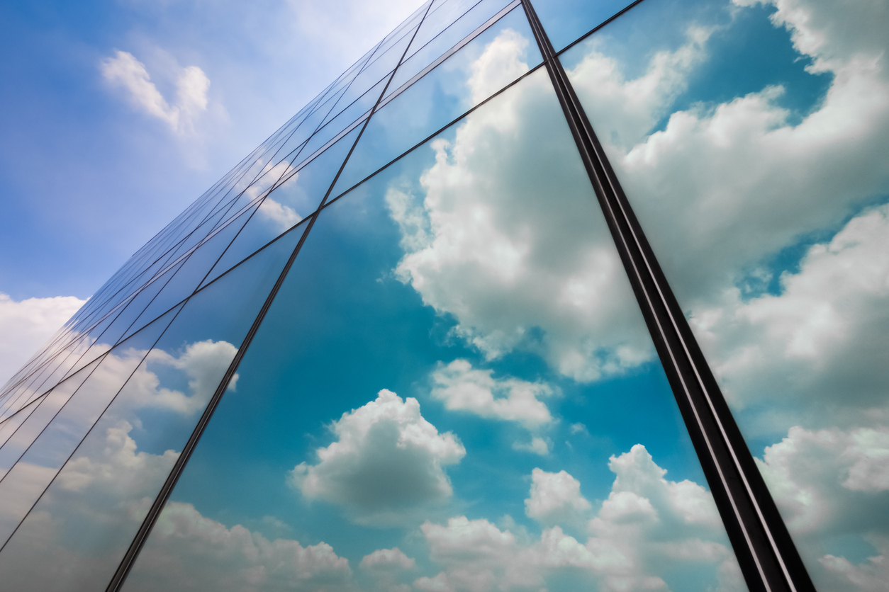 The exterior of a building with mirrored curtain wall, reflecting the sky and clouds