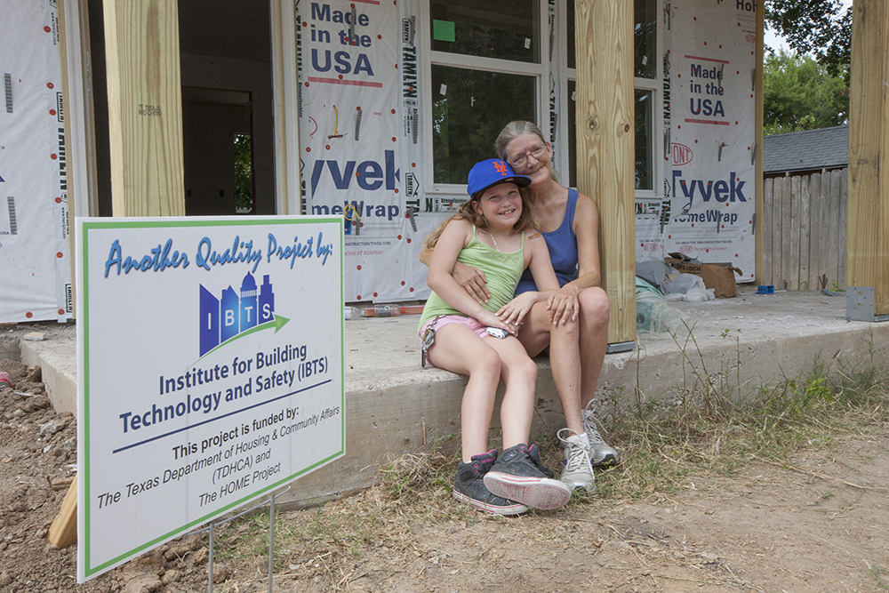An adult and child sit on the front porch of their home under construction.