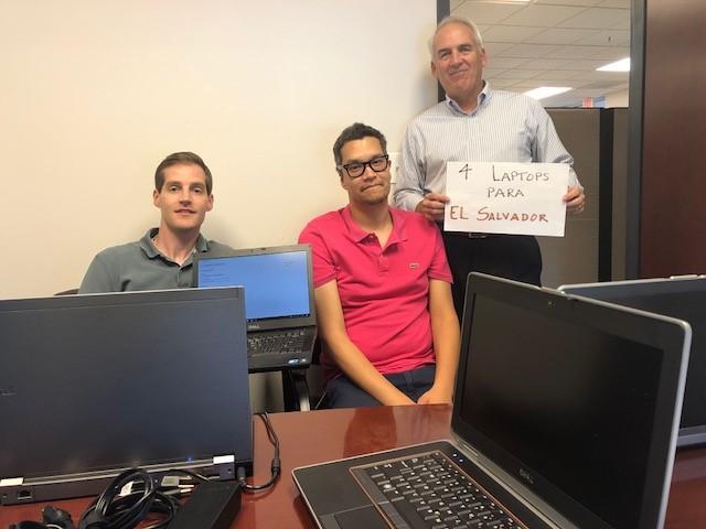 IBTS IT team members sit behind a desk.