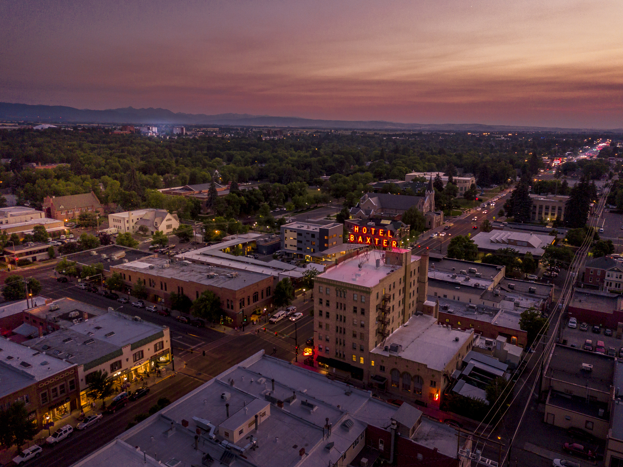 Aerial view of downtown Bozeman Montana at dusk. Main Street with lights twinkling from local businesses and vehicles.