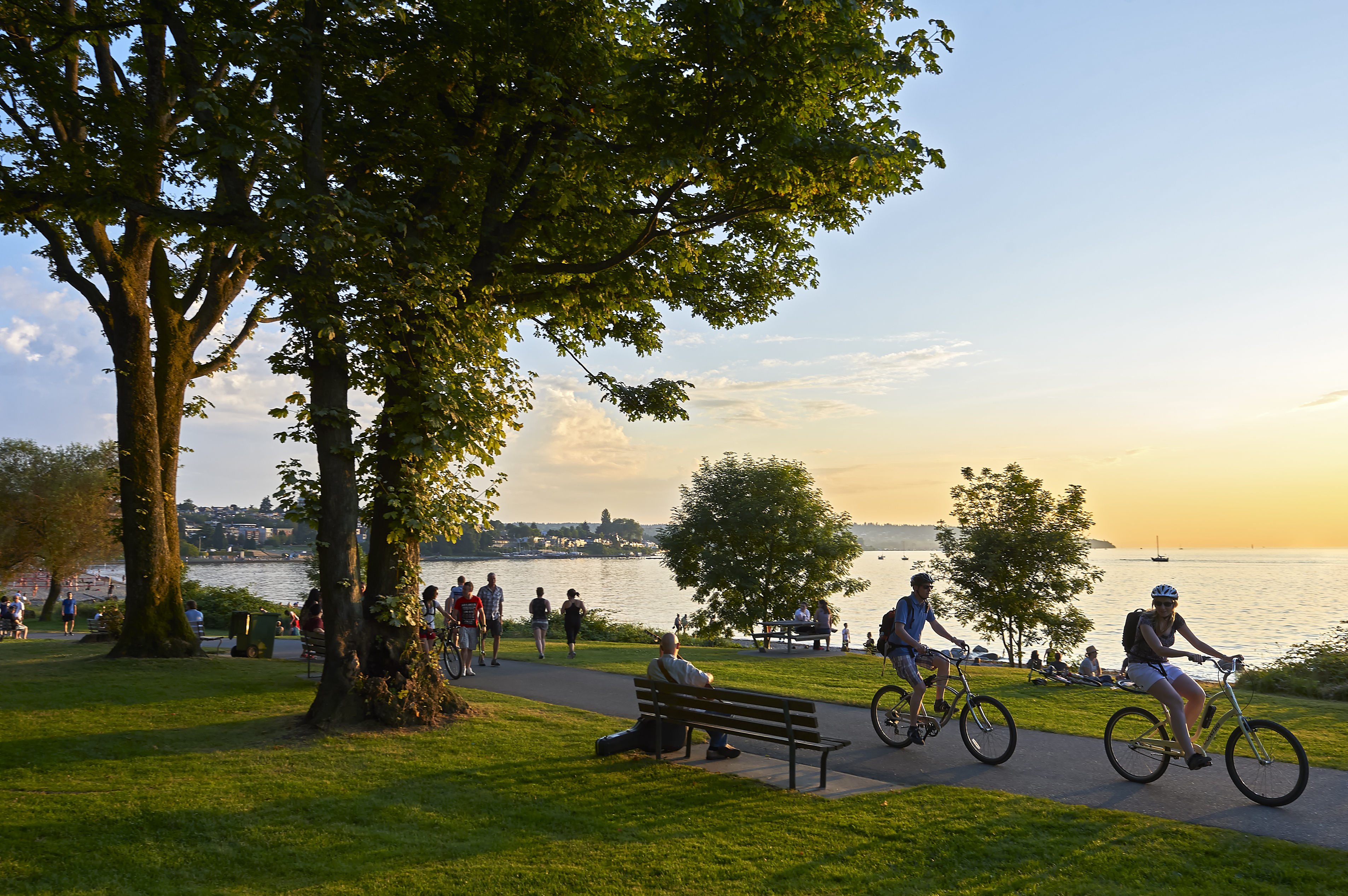 Young couple cycling, others walking or jogging late afternoon and enjoying the sunset at a lakefront park